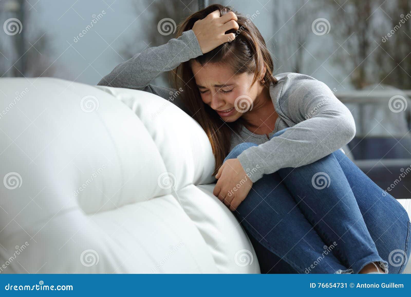 Унылая девушка плача самостоятельно дома