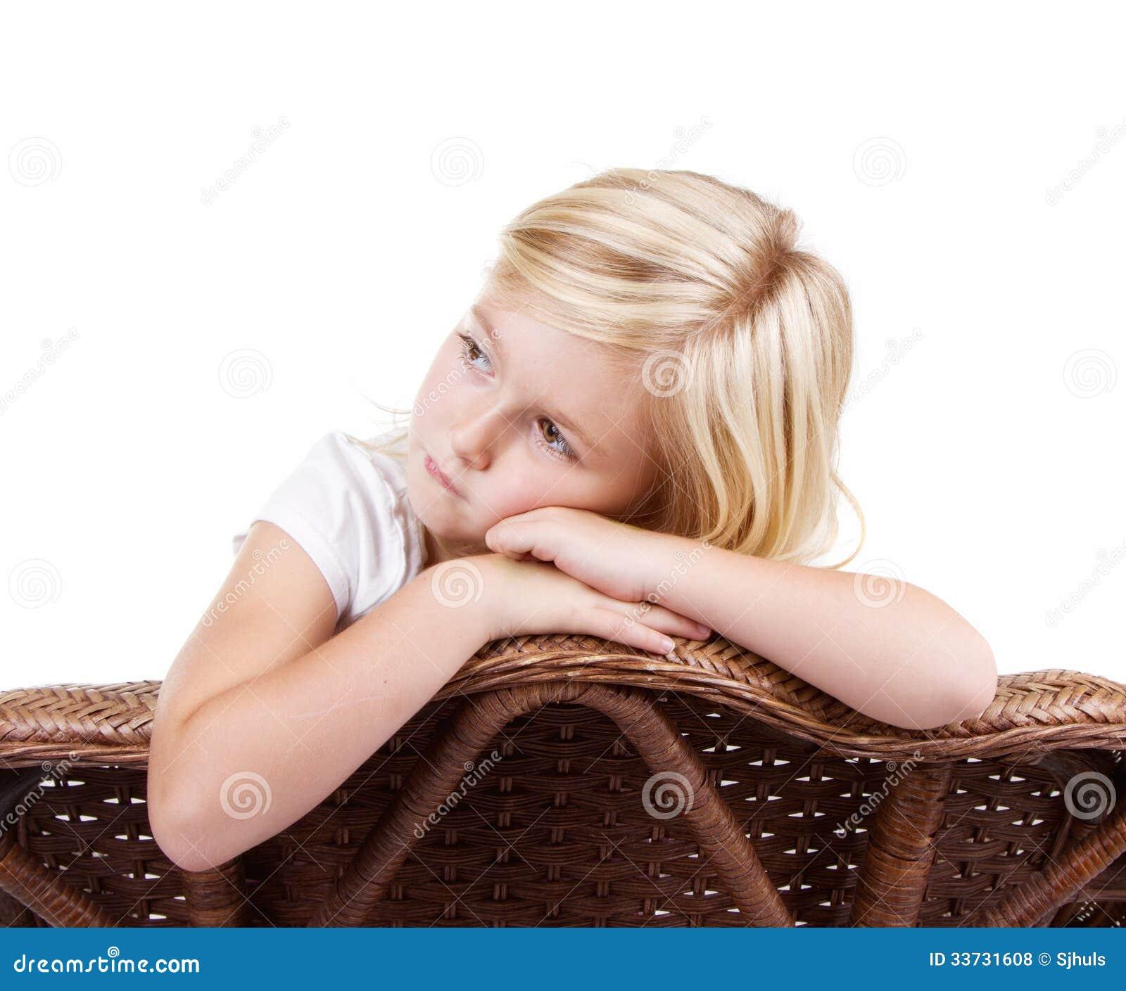 Унылая девушка сидя в стуле