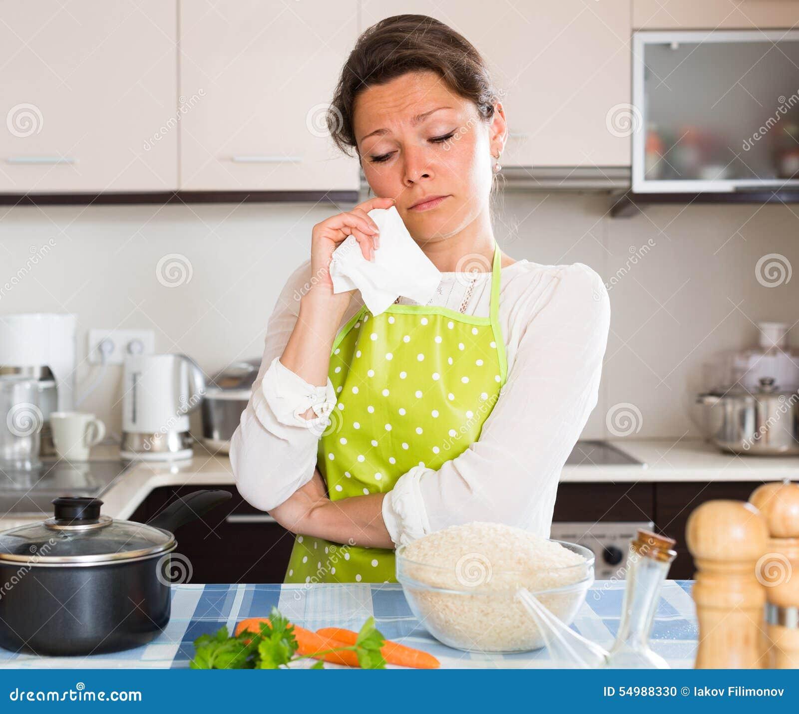 Унылая женщина варя рис в кухне
