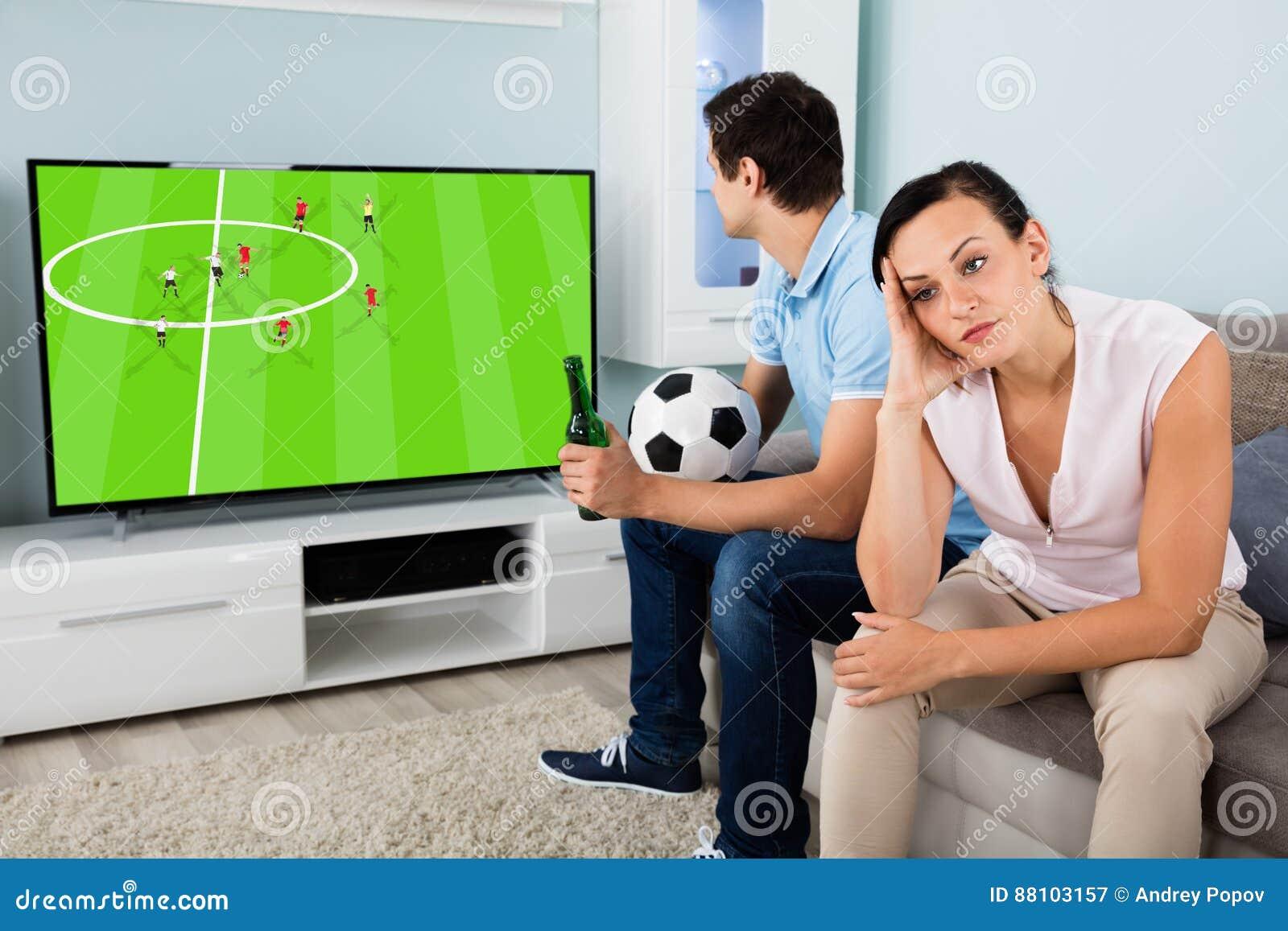 Унылая женщина сидя около человека занятого наблюдающ футбол