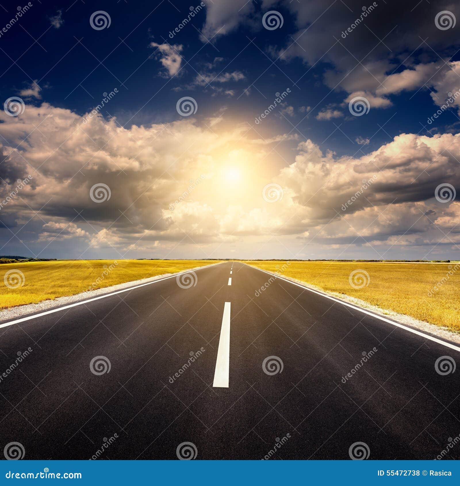 Управлять на пустой новой дороге асфальта на заходе солнца