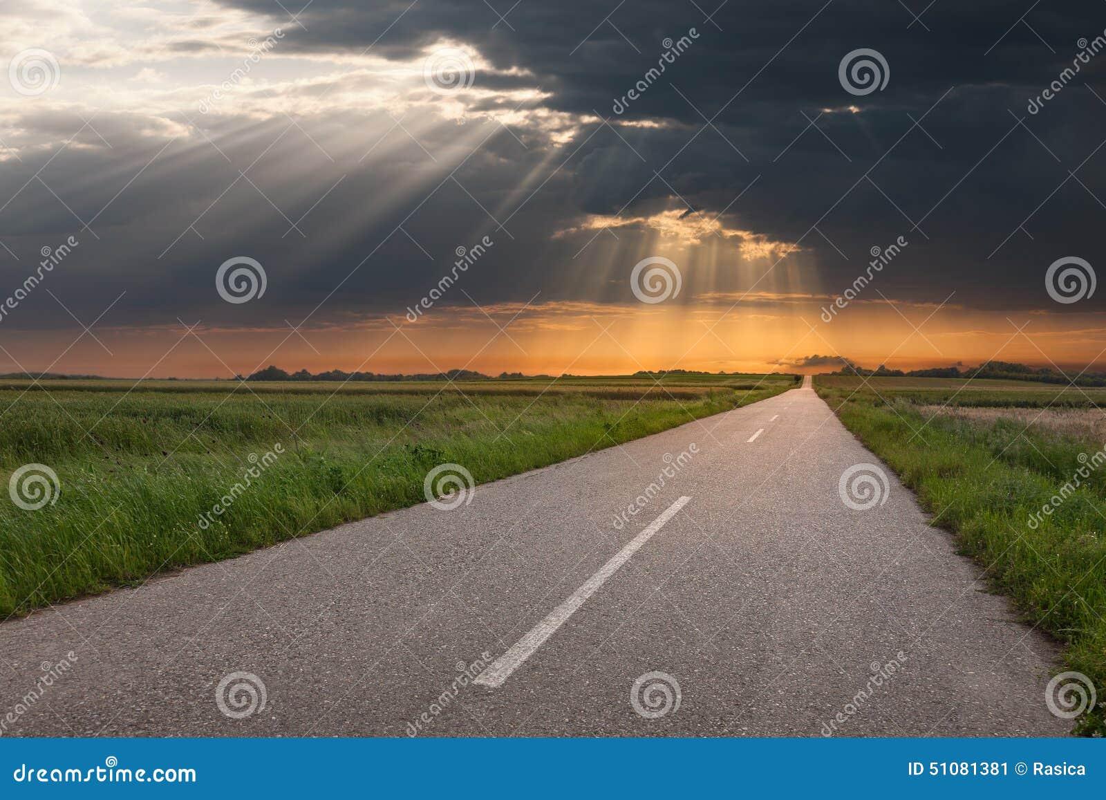 Управлять на пустой проселочной дороге на заходе солнца