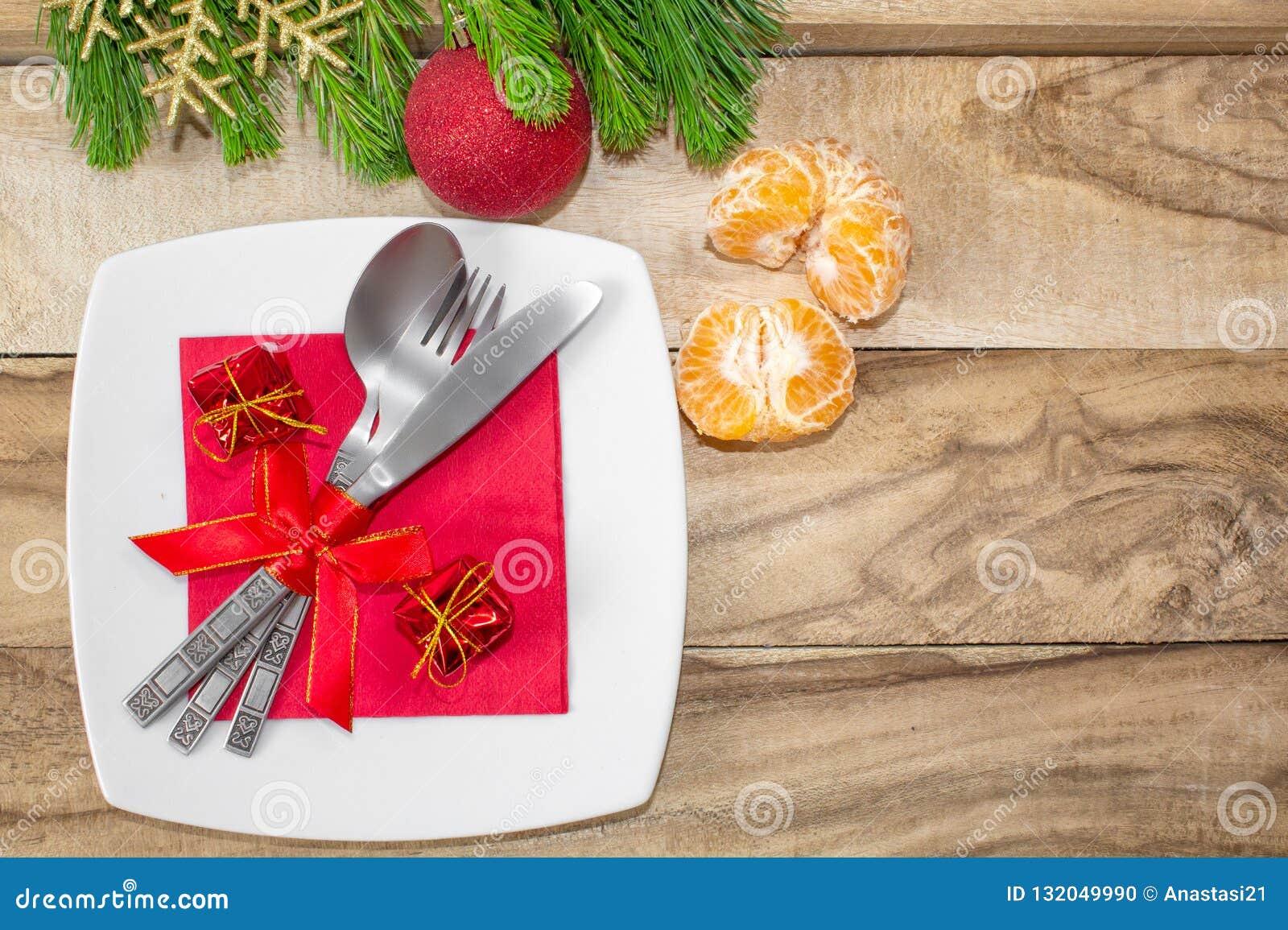 Урегулирование места таблицы рождества предпосылка праздничная Ветви ели, шариков, столового прибора и tangerines