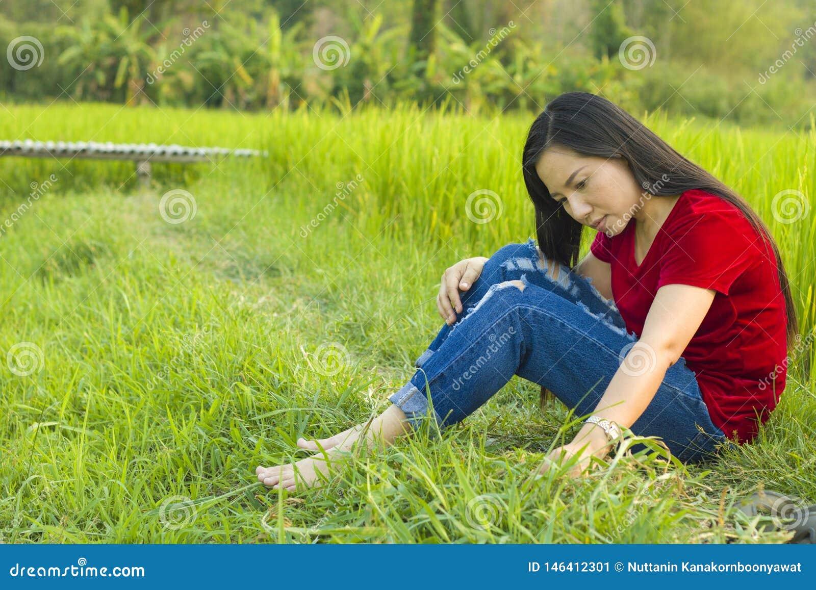 Усаживание предназначенной для подростков девушки азиатское в поле риса думая и усмехаясь счастливо напомненный о прошлого больше