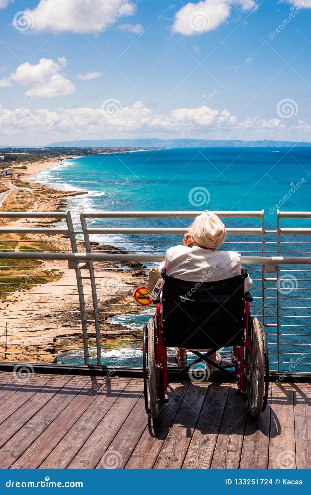 Усаживание старухи инвалидное на кресло-коляске и говоря мобильном телефоне пока смотрящ к северному побережью Средиземного моря