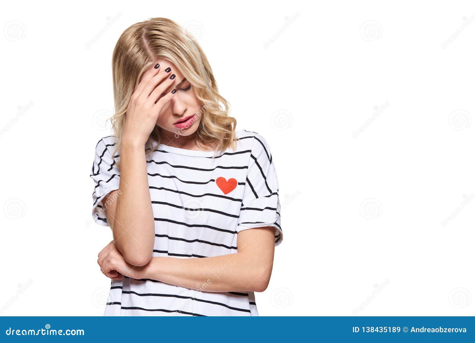 Усиленная вымотанная молодая студентка имея головную боль Давление и стресс чувства Подавленный студент с головой в руках