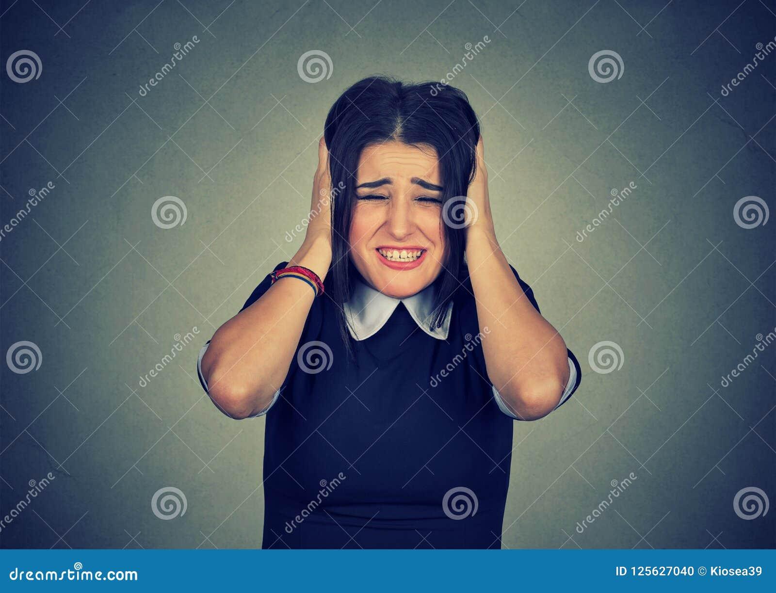 Усиленная женщина сжимая голову с руками