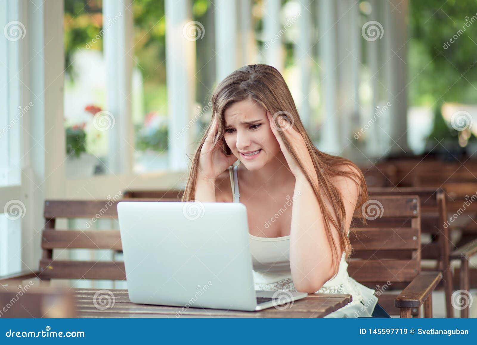 Усиленное грустное уставшее чувства женщины потревоженное на ноутбуке