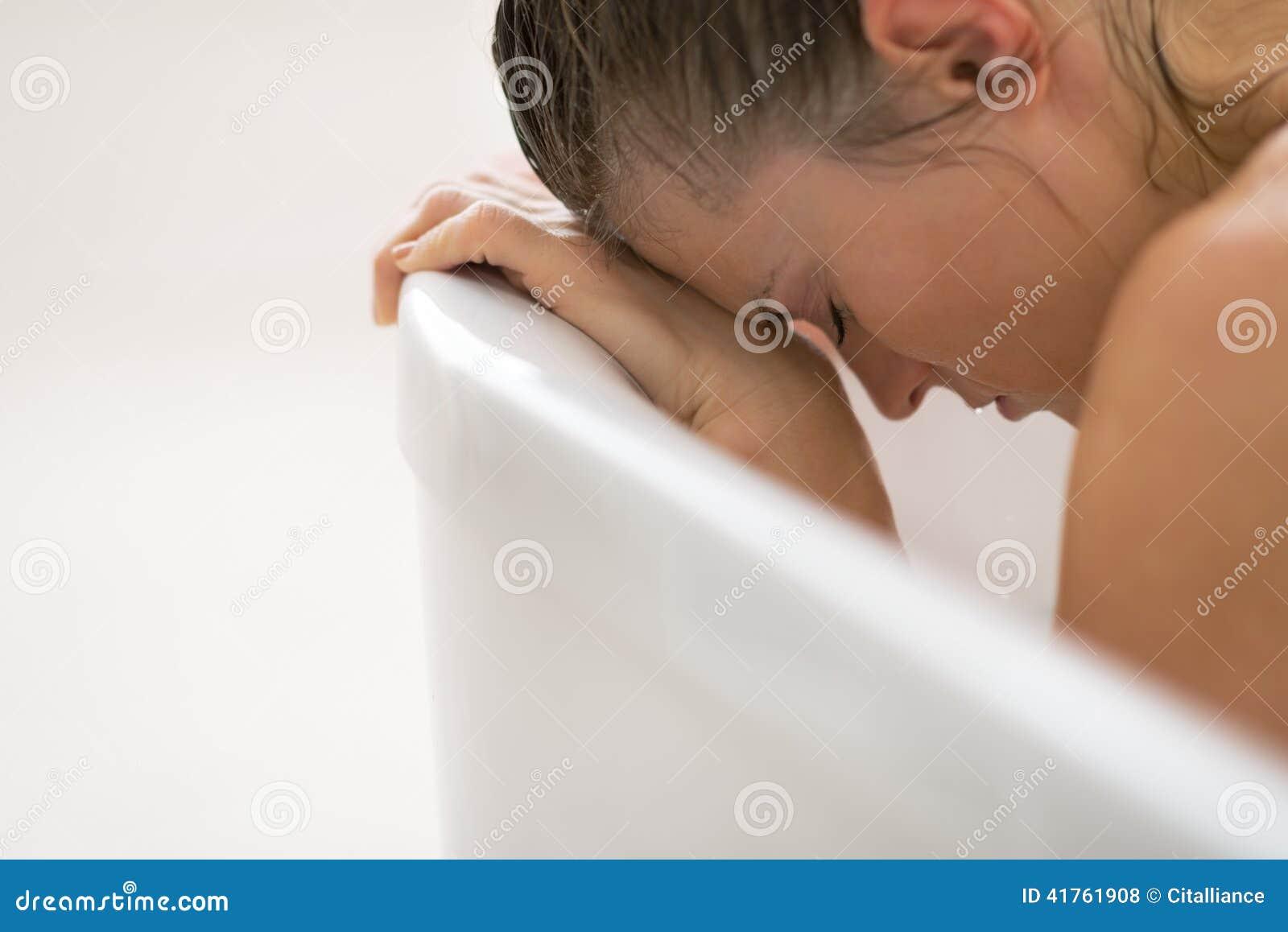 Усиленная молодая женщина сидя в ванне