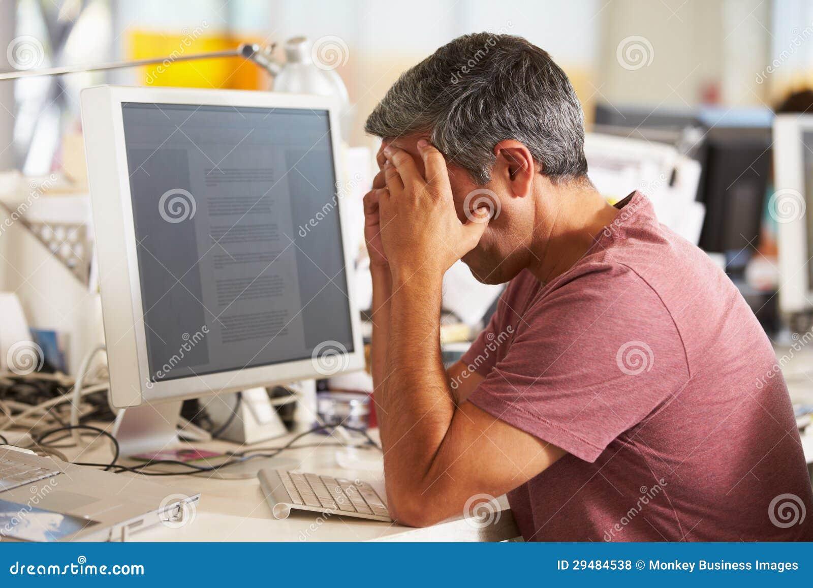 Усиленный человек работая на столе в многодельном творческом офисе