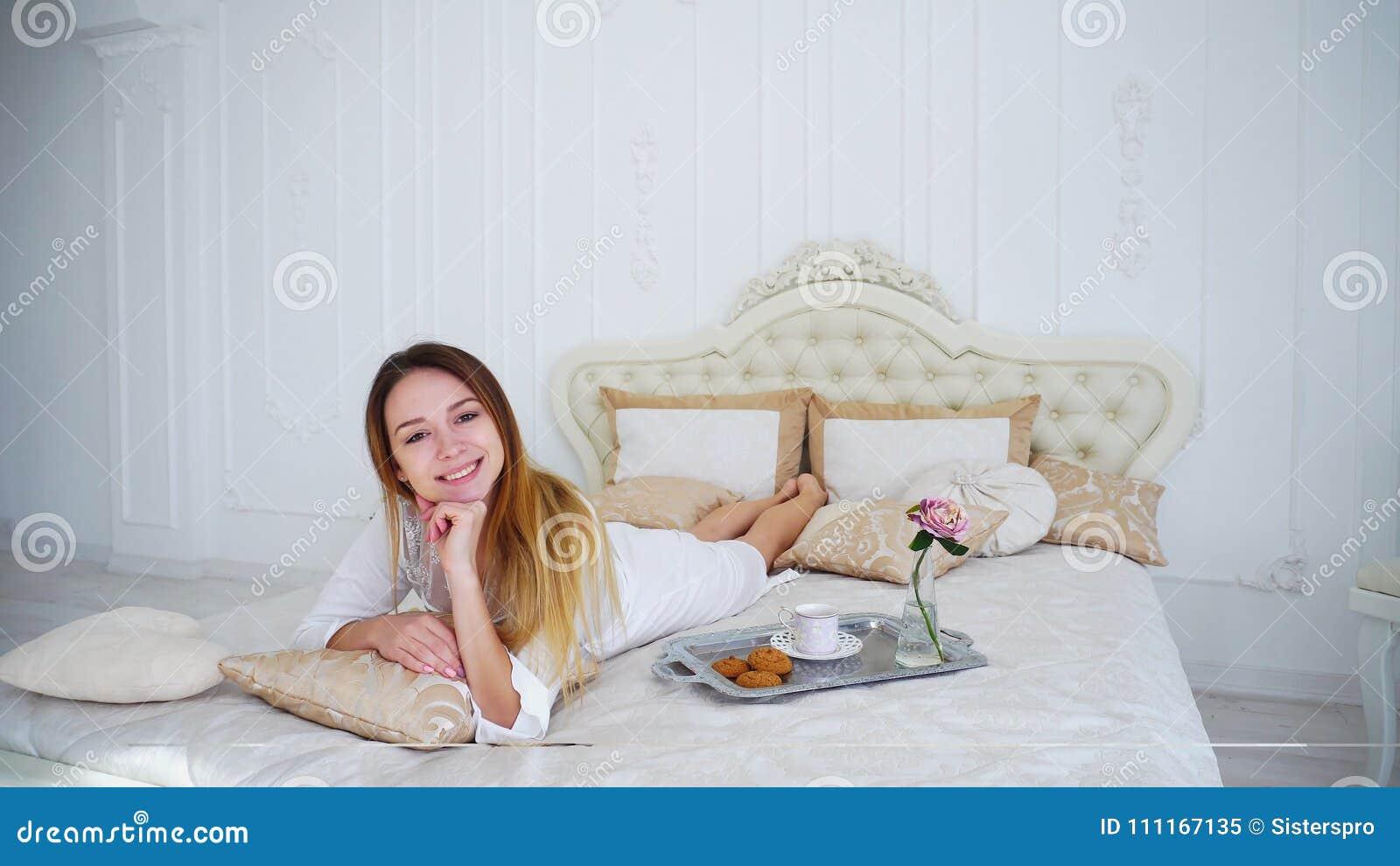 Усмехаться девушки модельный на камере лежа на кровати в яркой спальне