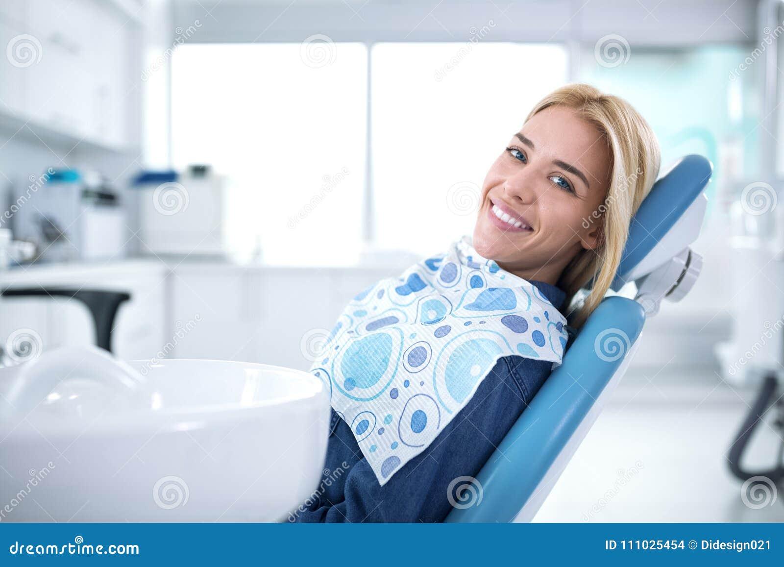 Усмехаться и удовлетворенный пациент в зубоврачебном офисе