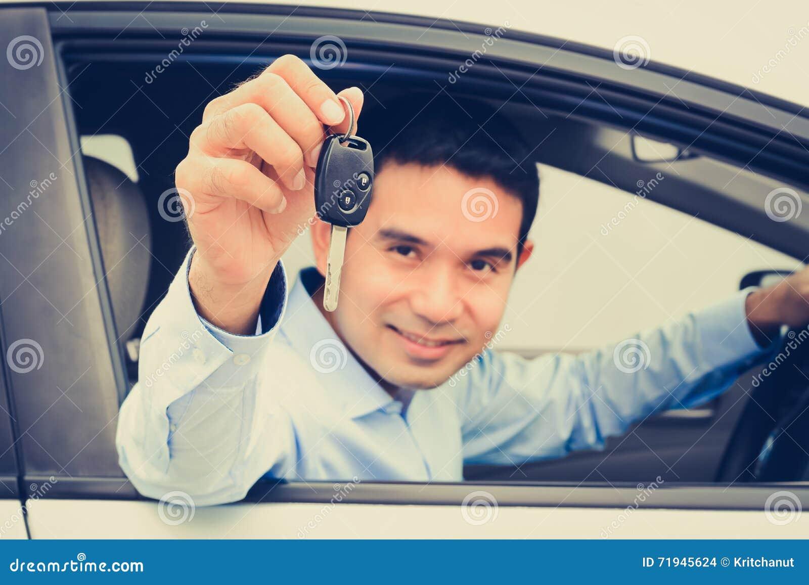 Усмехаясь азиатский человек как водитель показывая ключ автомобиля (сфокусированный ключ)