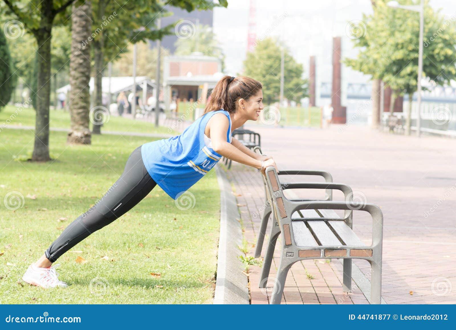 Усмехаясь атлетическая женщина делать нажимает поднимает в улице, здоровом lif
