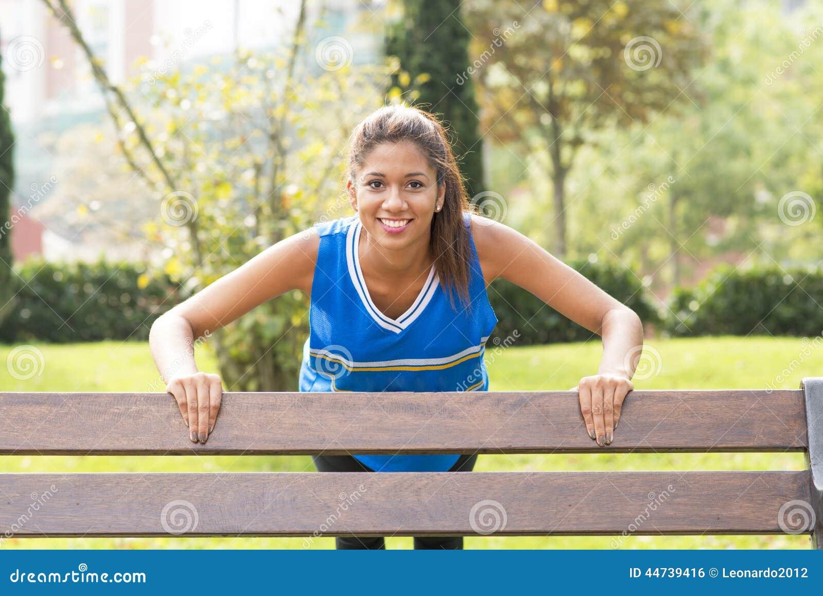 Усмехаясь атлетическая женщина делая pushups на стенде