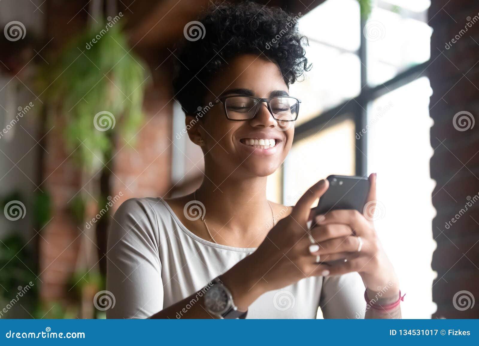 Усмехаясь Афро-американская женщина используя телефон, получает хорошее сообщение