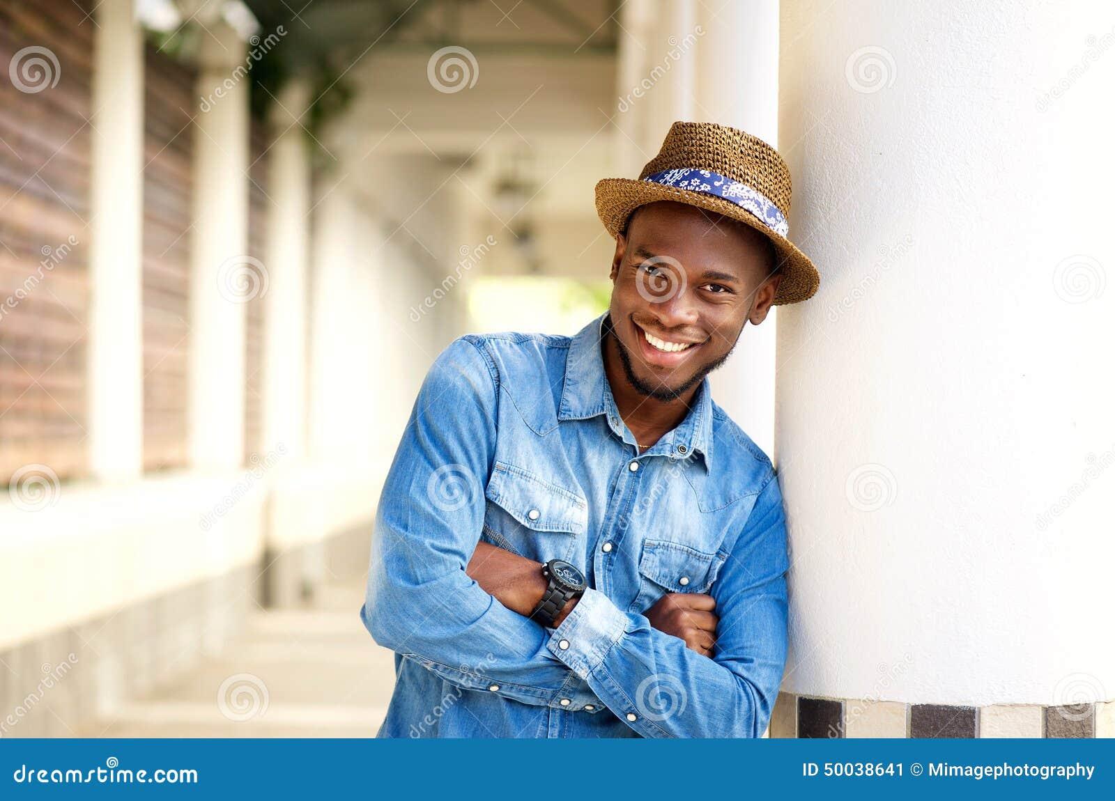Усмехаясь Афро-американский человек ослабляя при пересеченные оружия