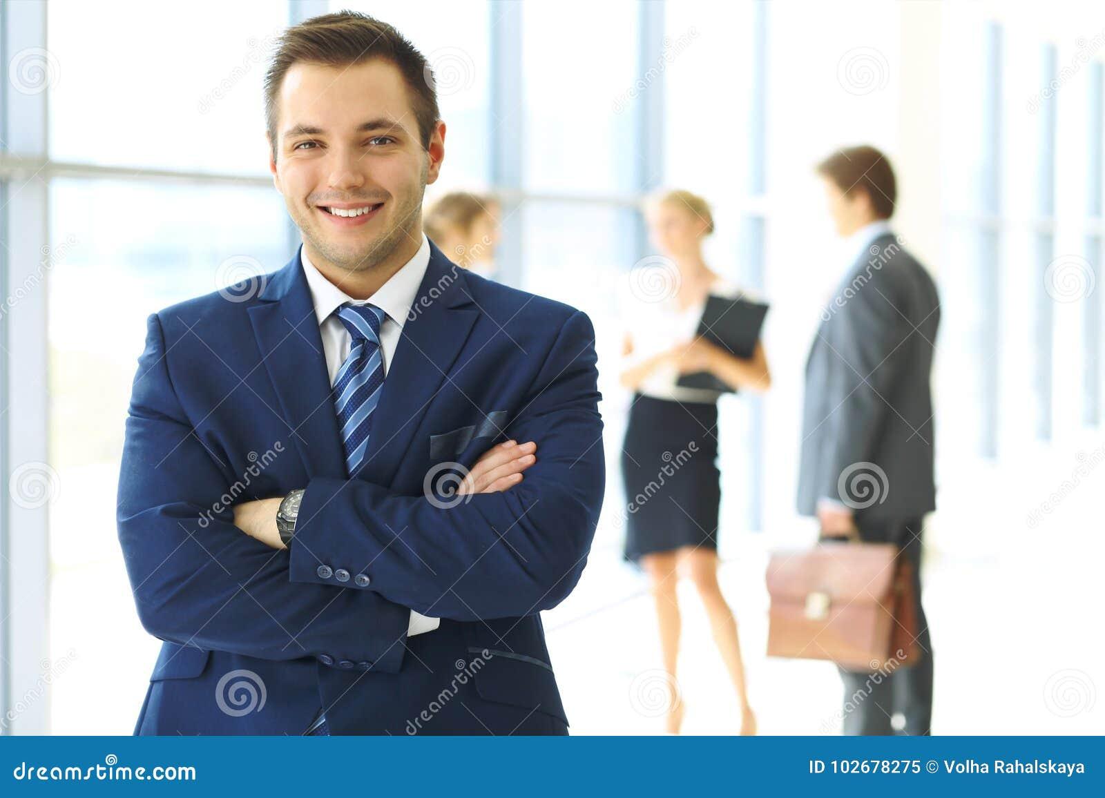 Усмехаясь бизнесмен в офисе с коллегами на заднем плане