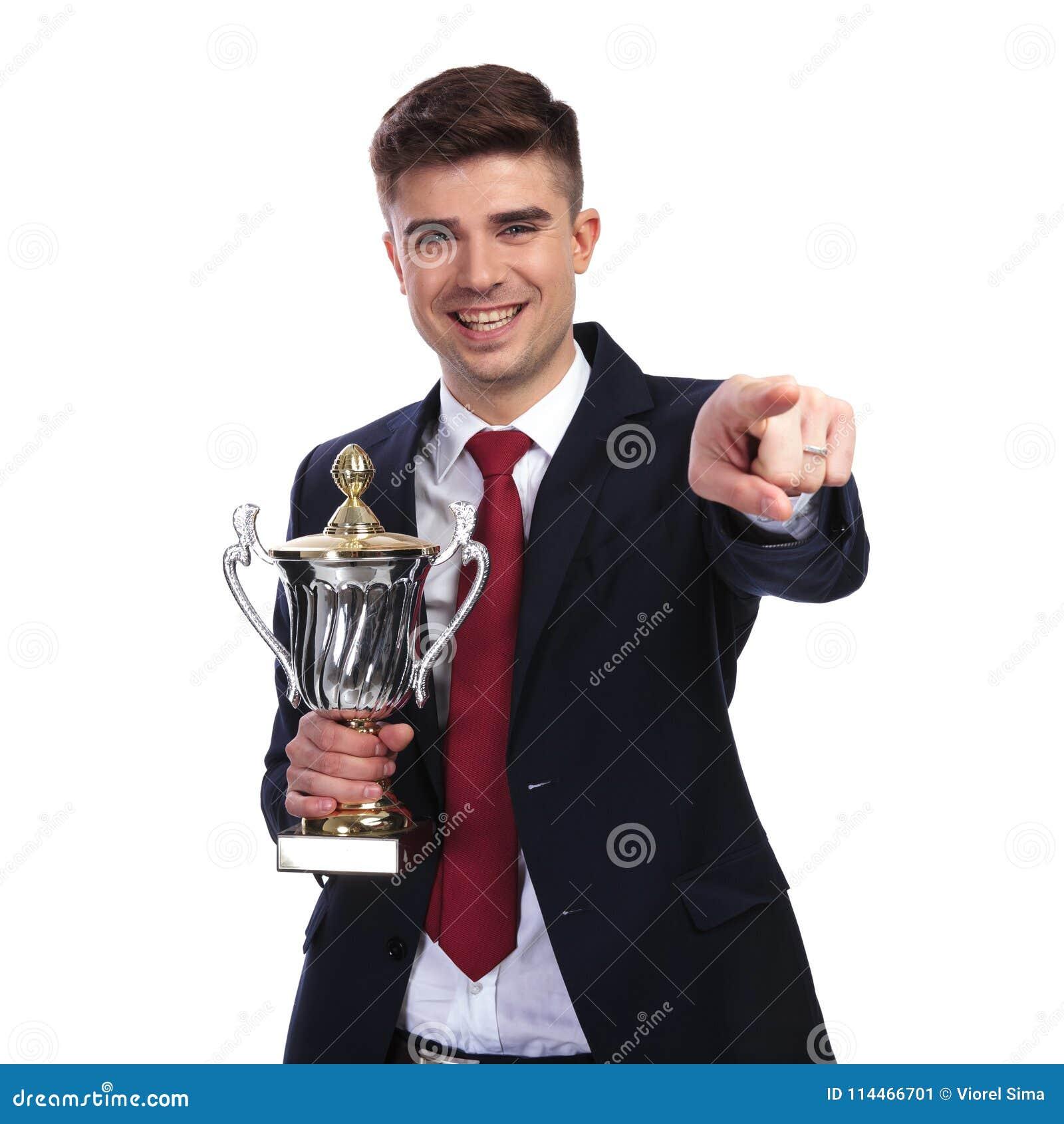 Усмехаясь бизнесмен указывает палец пока держащ награженное trop