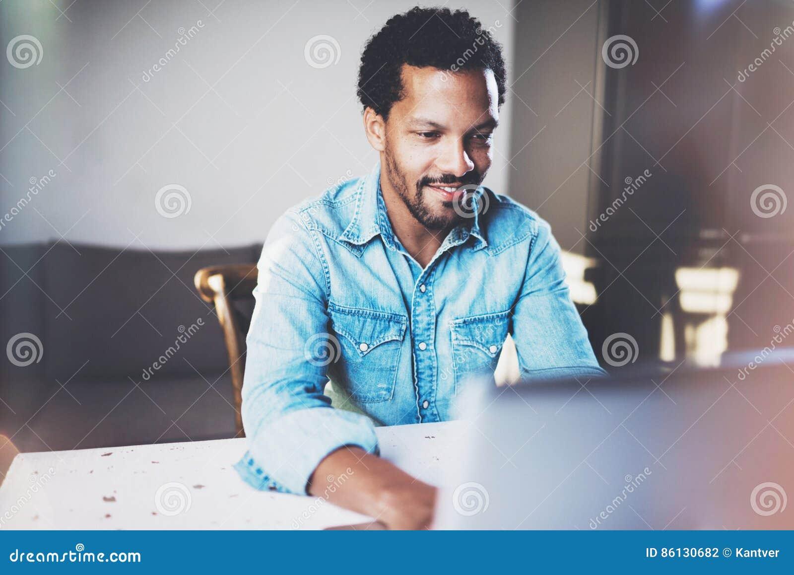Усмехаясь бородатый африканский человек работая на компьтер-книжке пока тратящ время на coworking офисе Концепция молодых бизнесм