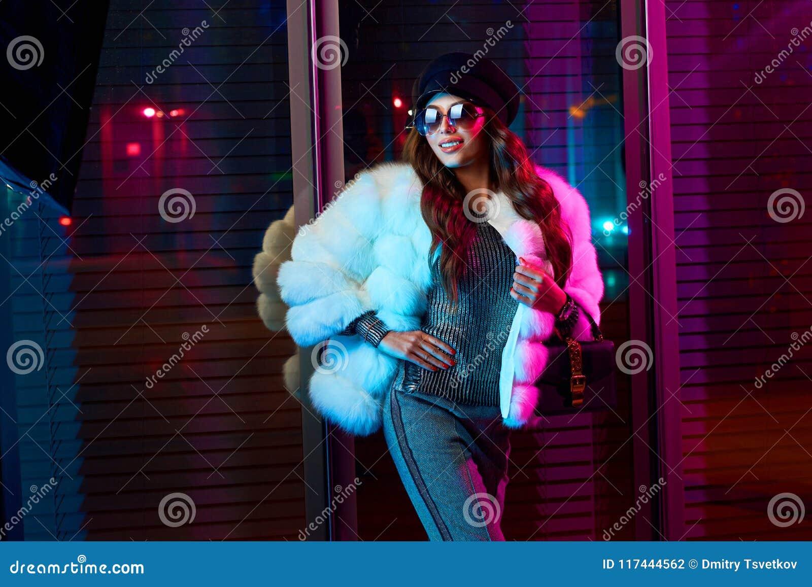 Усмехаясь девушка в ультрамодной белой меховой шыбе и солнечных очках