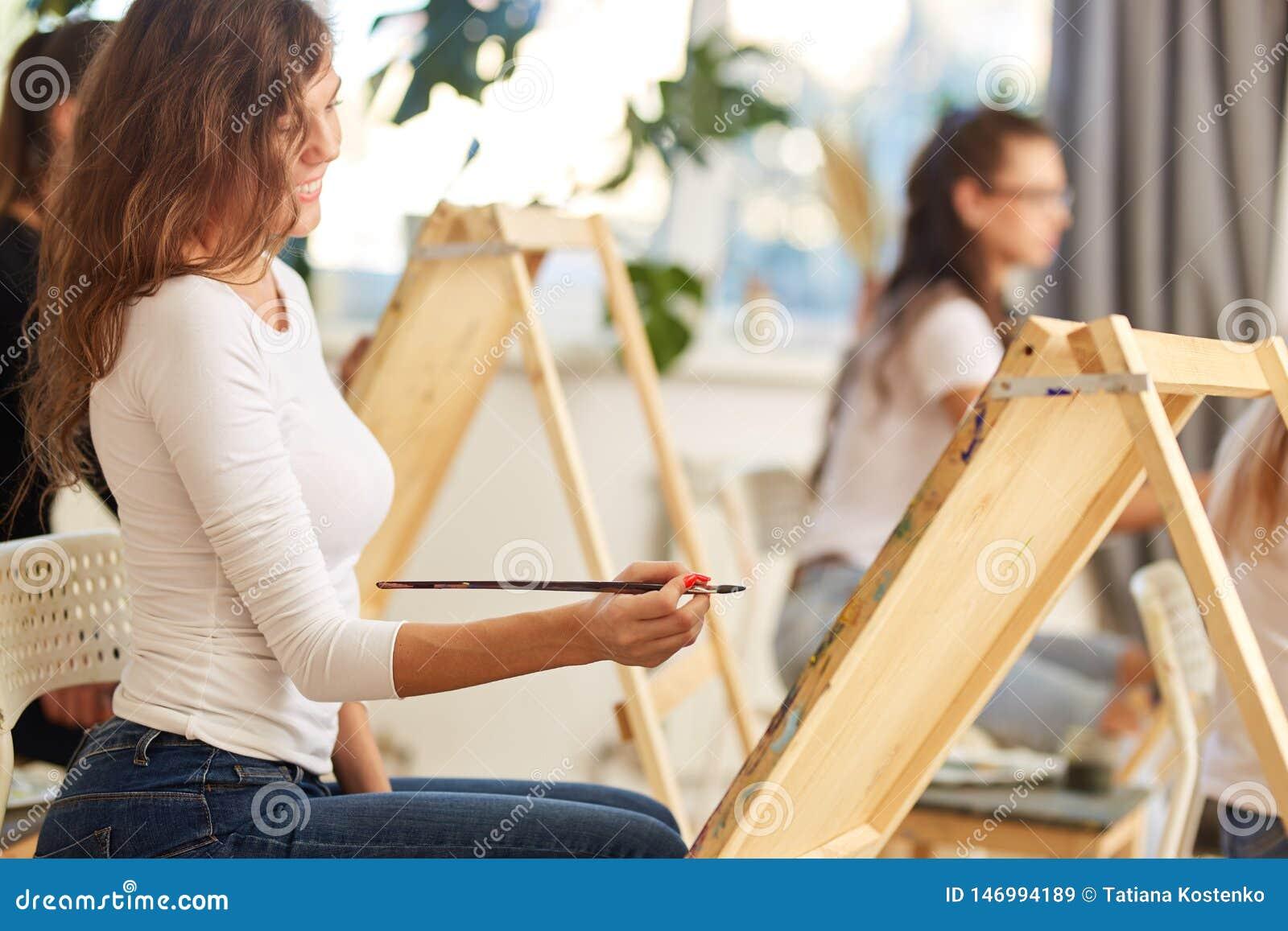 Усмехаясь девушка с коричневым вьющиеся волосы одетым в белой блузке красит изображение на мольберте в рисуя школе