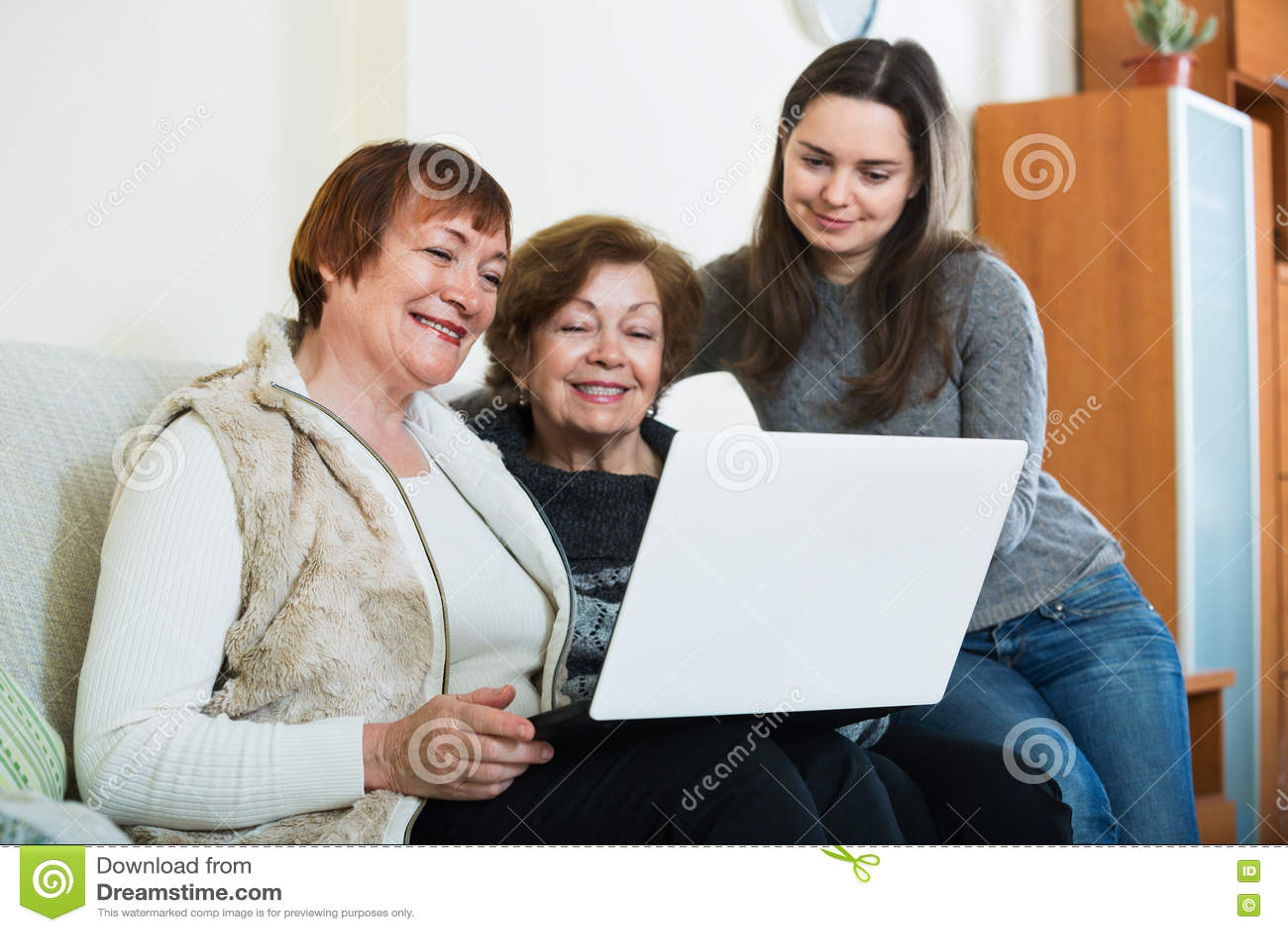 Усмехаясь девушка уча положительным старшим женщинам используя компьтер-книжку