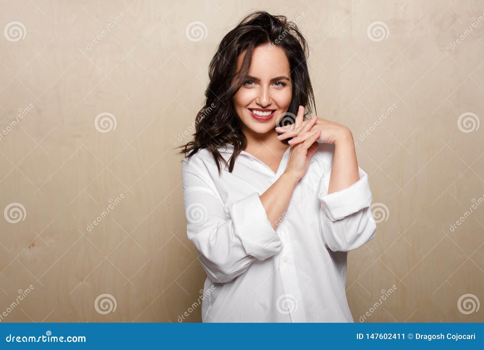 Усмехаясь женская модель в белой рубашке, на бежевой предпосылке, держа пересеченные пальцы