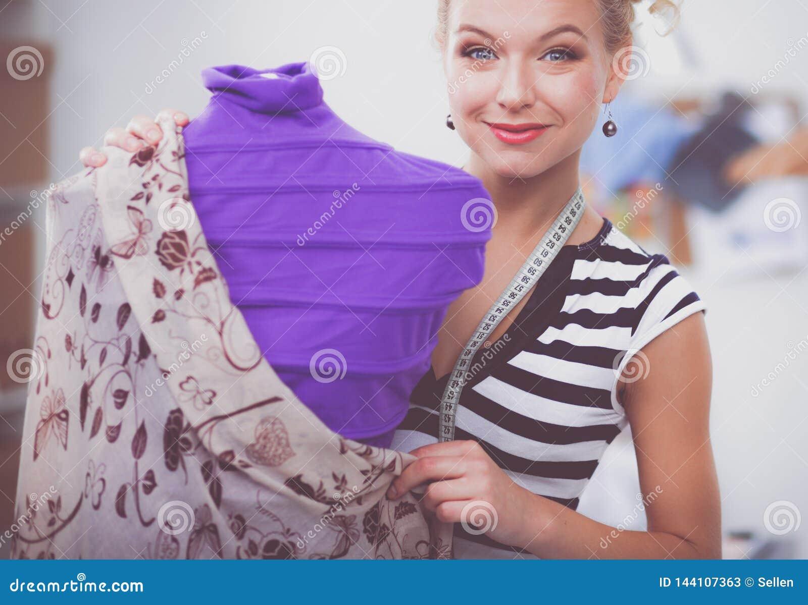 Усмехаясь женщина модельера стоя близко манекен в офисе
