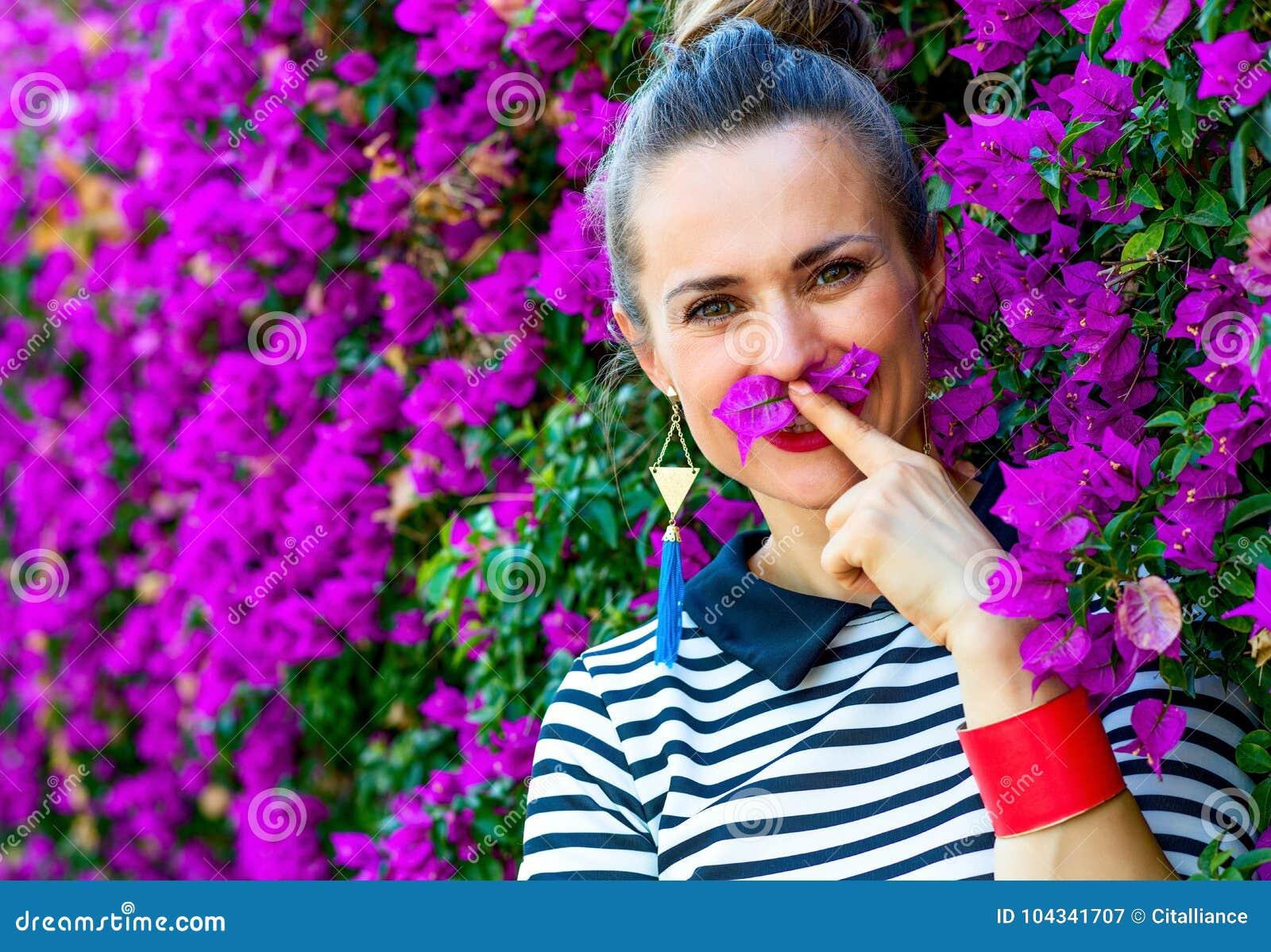 Усмехаясь женщина около красочной magenta кровати цветков имея время потехи