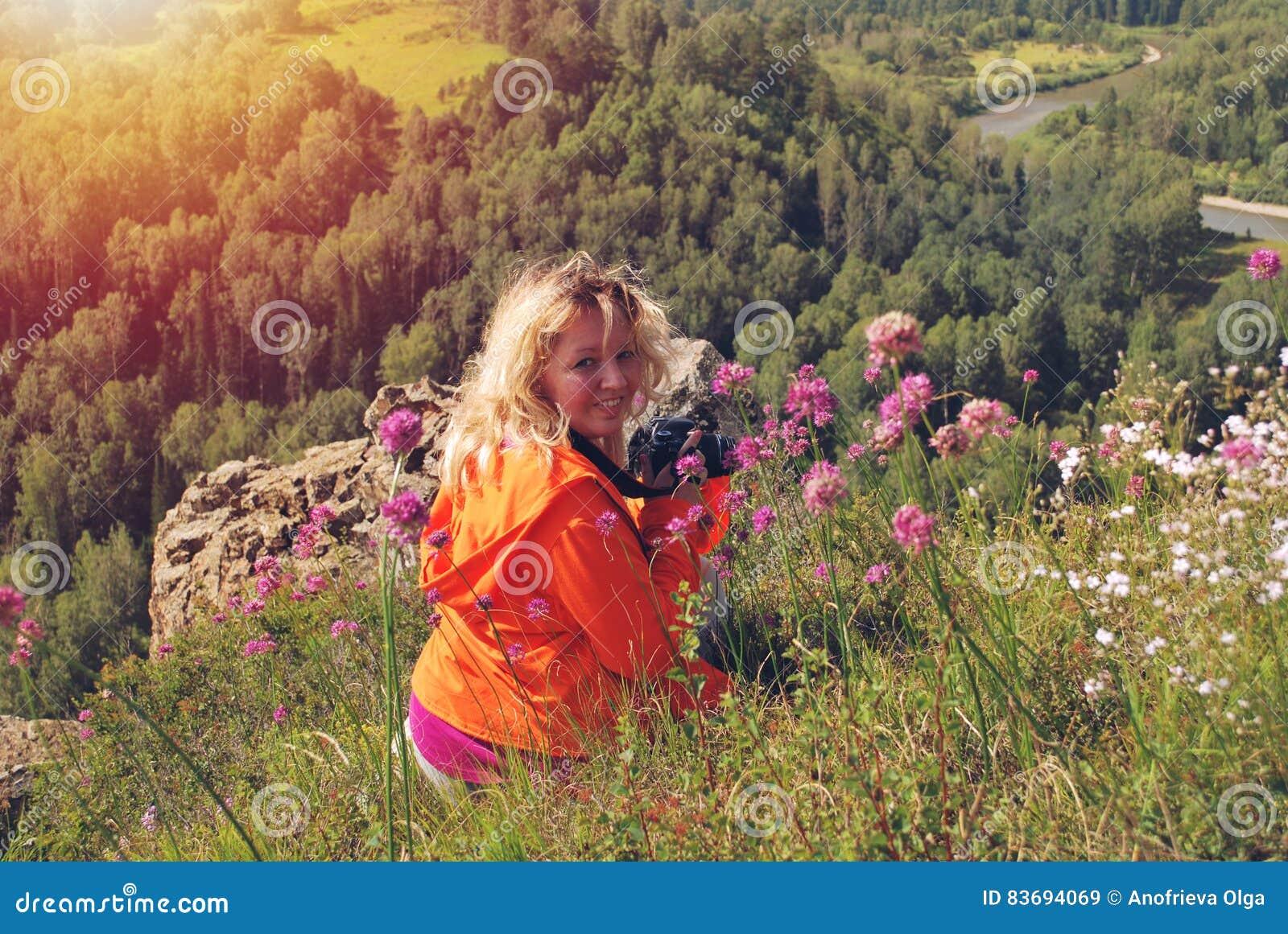 Усмехаясь женщина с камерой наверху горы