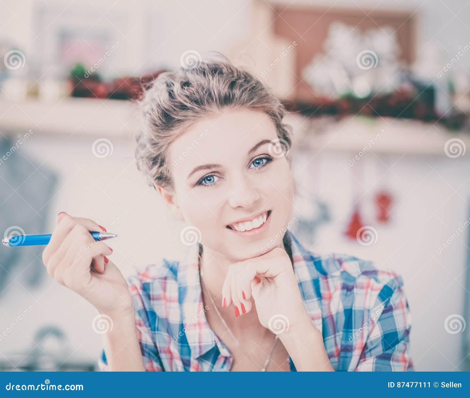 Усмехаясь женщина с чашкой кофе и газетой в кухне