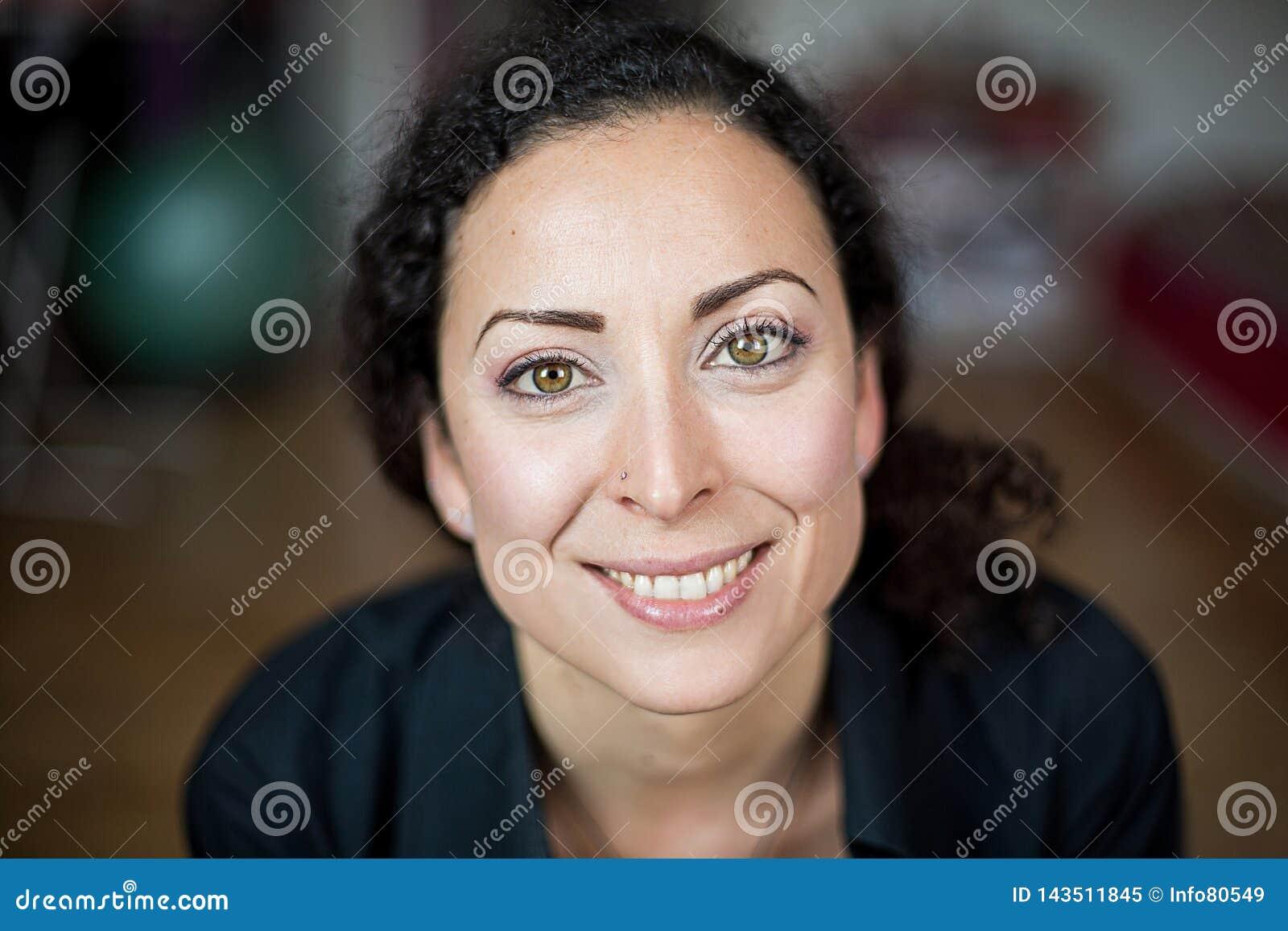 Усмехаясь, жизнерадостная и дружелюбная женщина с зелеными глазами с красочной предпосылкой
