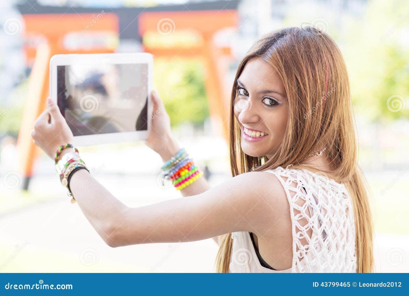 Усмехаясь красивая девушка фотографируя с планшетом в t