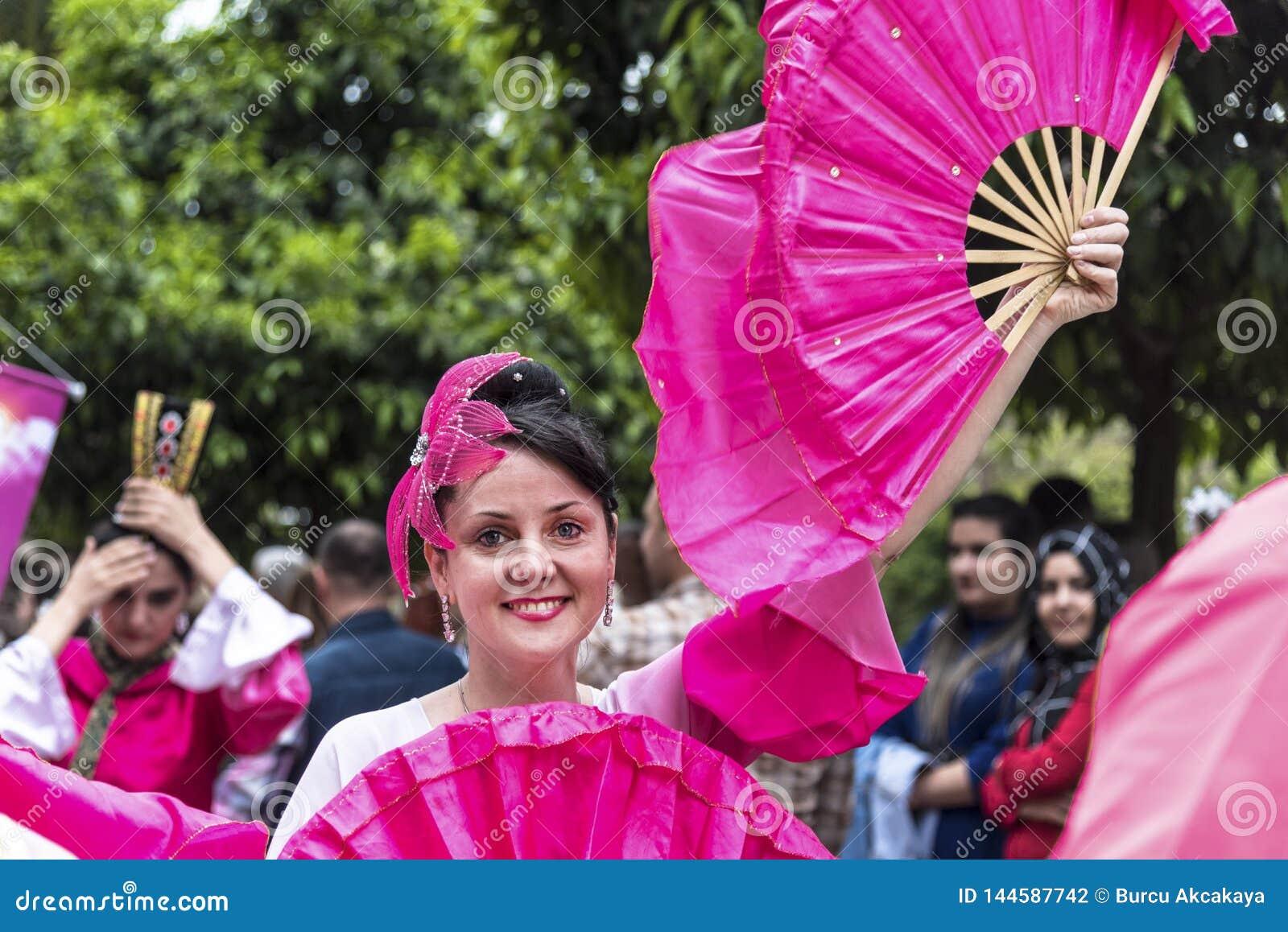 Усмехаясь красивая женщина с pinky вентилятором руки и розовым костюмом в оранжевом отверстии парада масленицы цветения Adana - Т