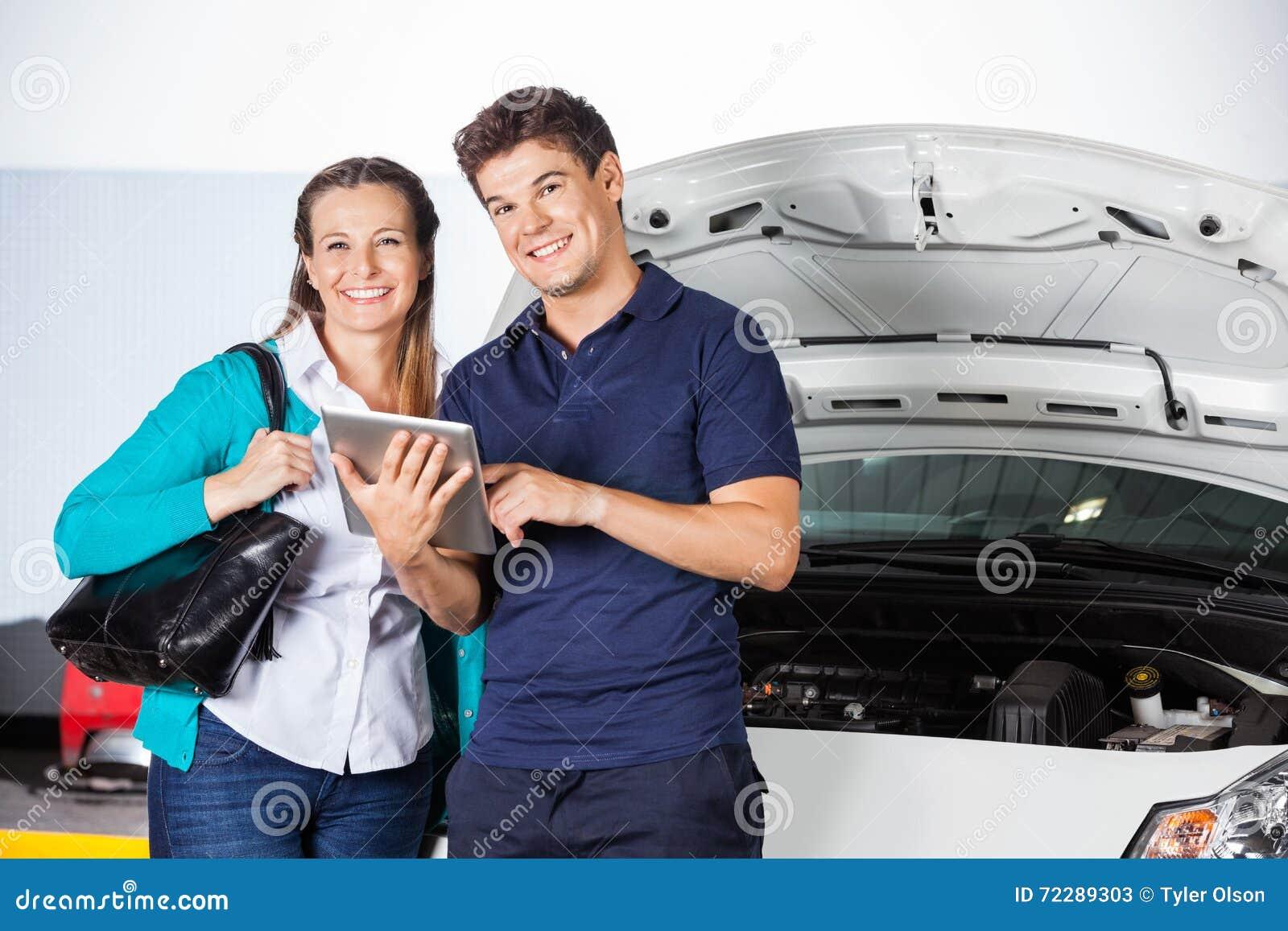 Download Усмехаясь клиент стоя при механик держа таблетку цифров Стоковое Изображение - изображение насчитывающей магазин, заказ: 72289303