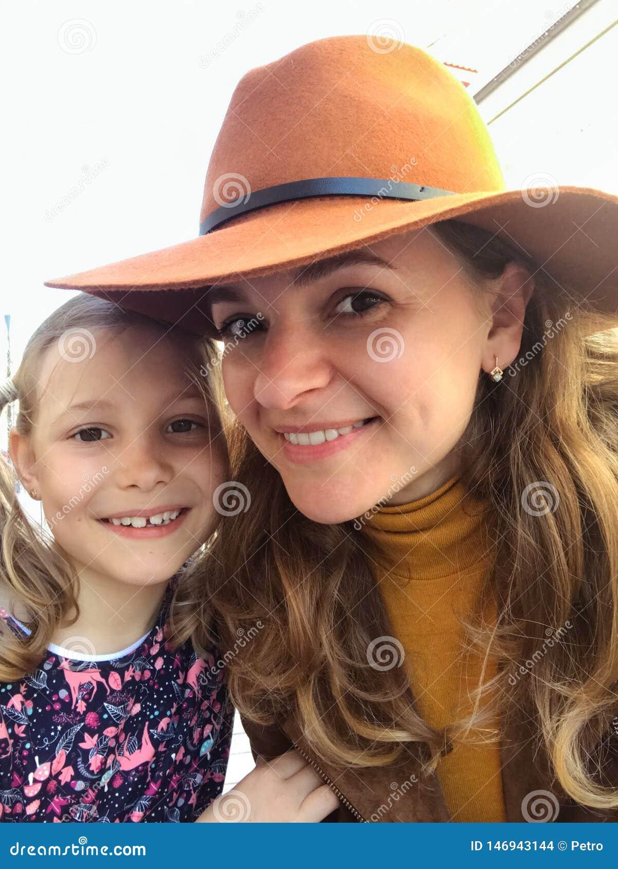 Усмехаясь мать и дочь смотря камеру