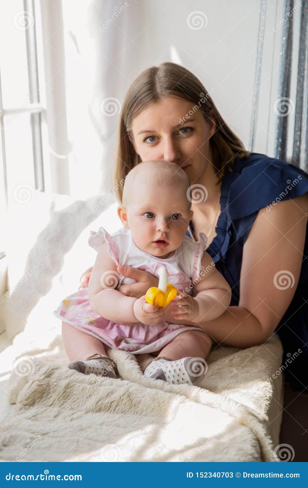 Усмехаясь мать обнимая ее дочь младенца на окне