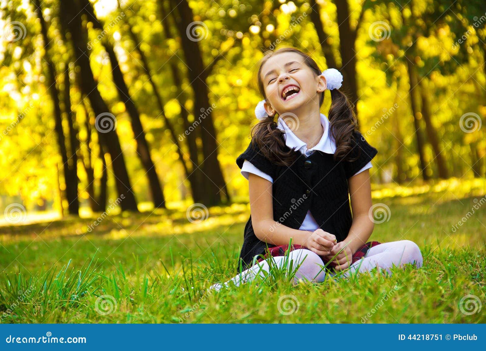 Усмехаясь маленькая девочка сидя на траве
