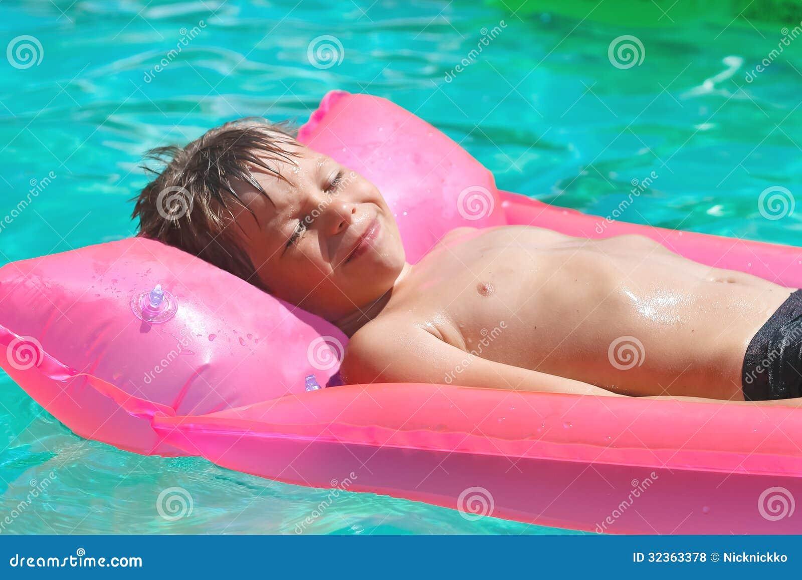 Усмехаясь мальчик лежит на розовом тюфяке