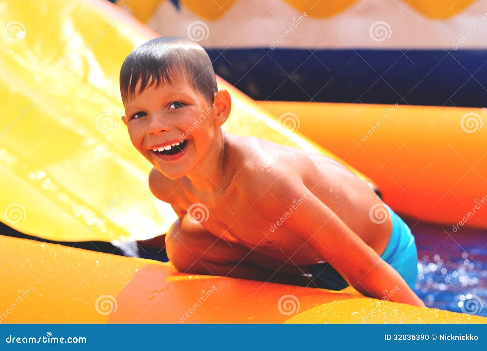 Усмехаясь мальчик около waterslide