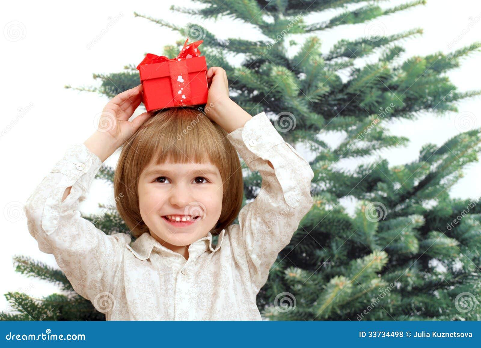 Усмехаясь мальчик с подарком в красной коробке