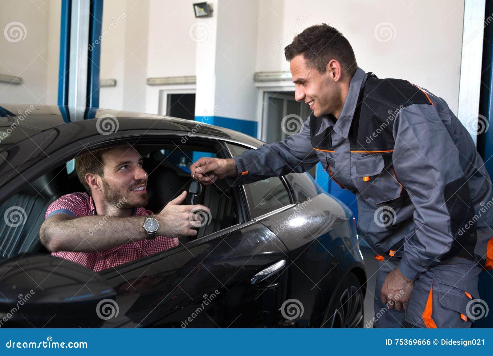 Усмехаясь механик возвращает ключ к удовлетворенному клиенту