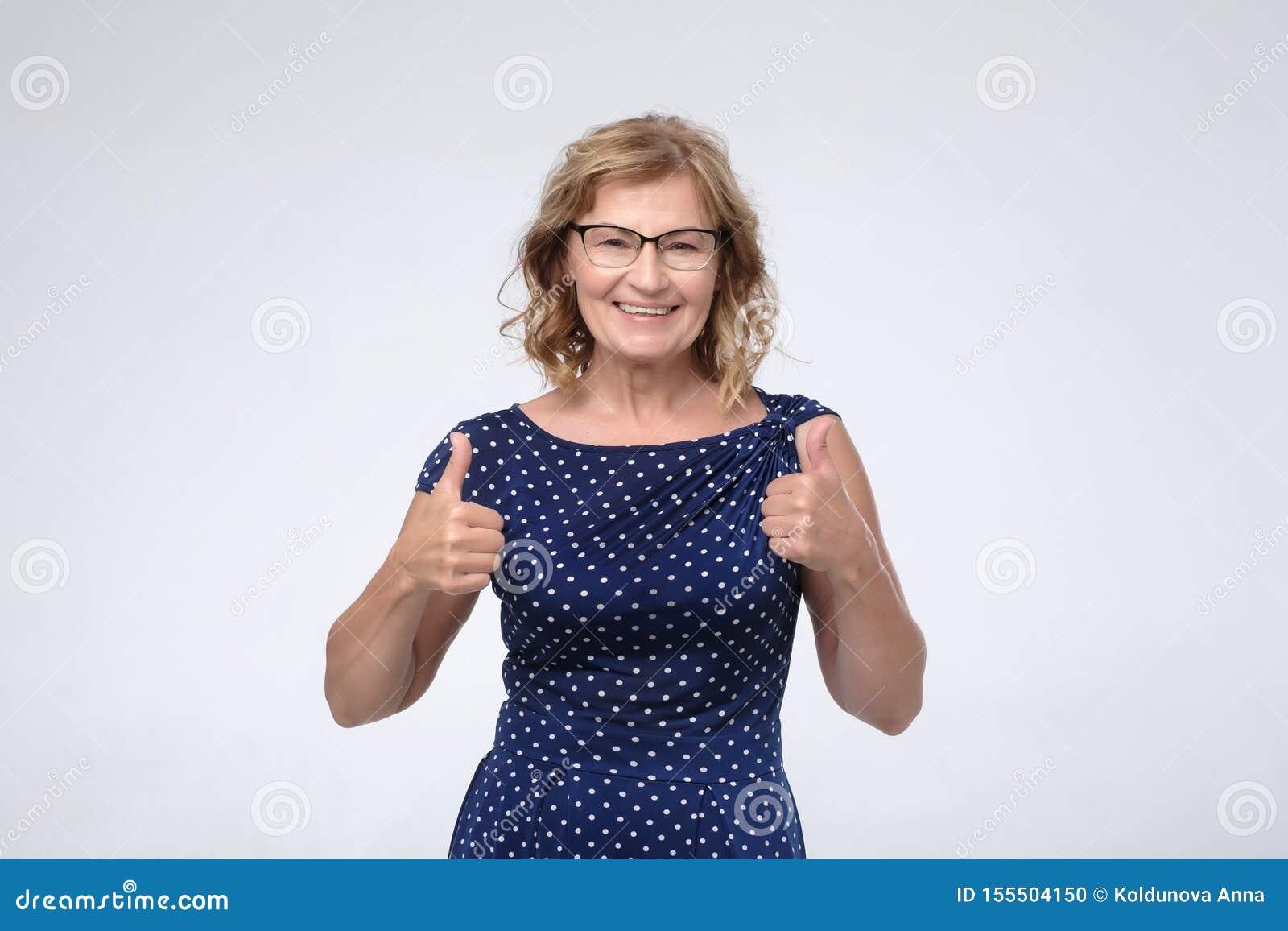 Усмехаясь милая зрелая женщина показывая большие пальцы руки вверх