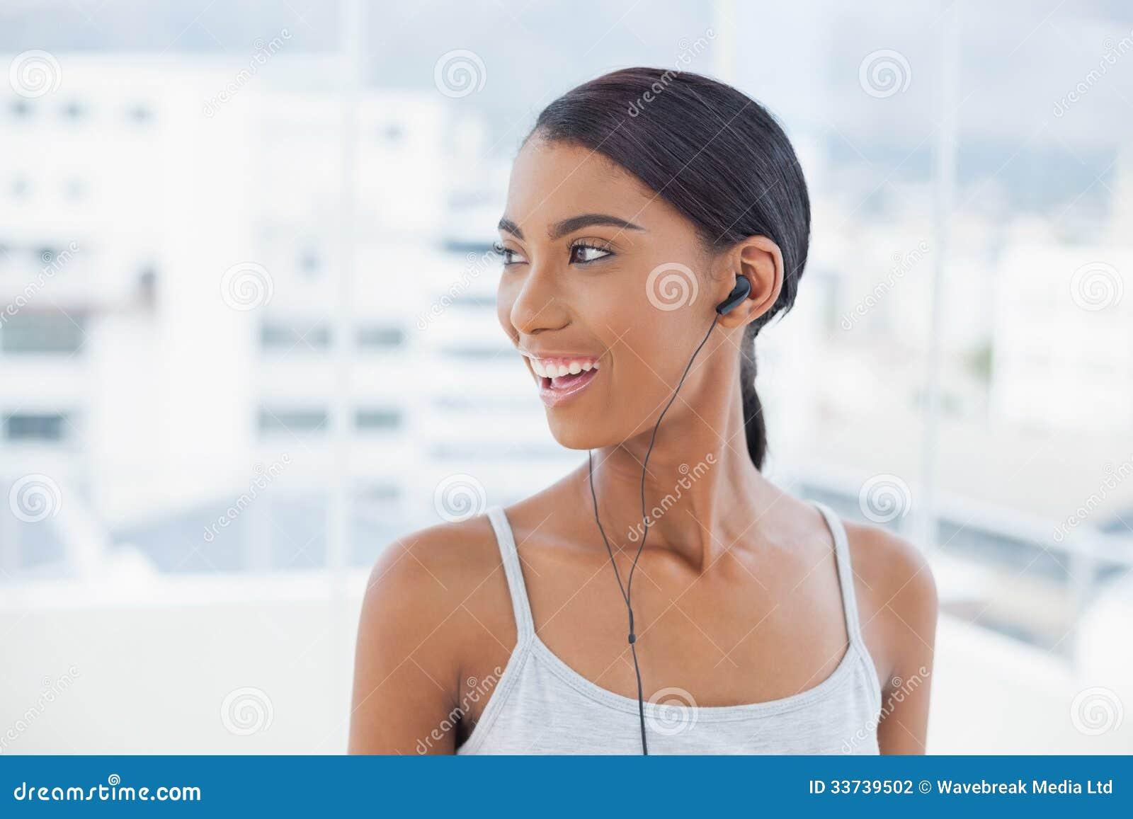 Усмехаясь милая модель слушая к музыке