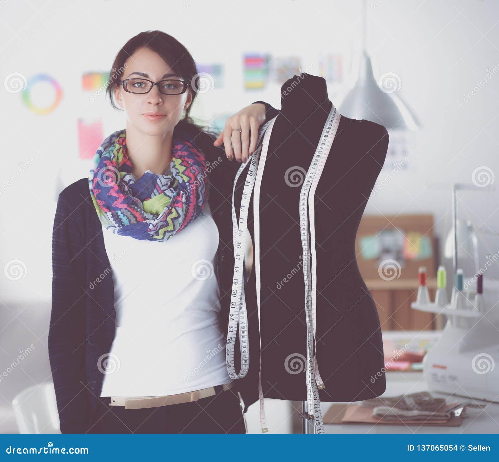 Усмехаясь модельер стоя близко манекен в офисе