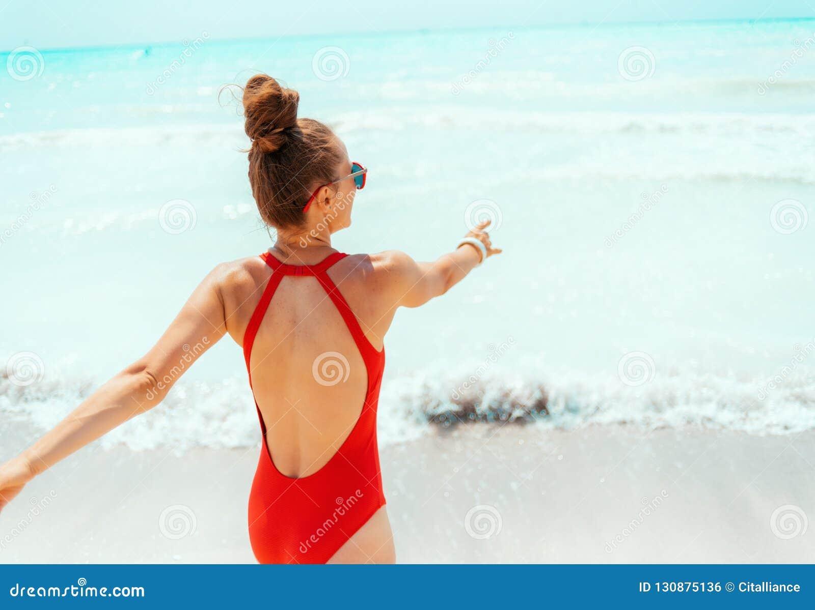 Усмехаясь молодая женщина в красном beachwear на пляже имея время потехи