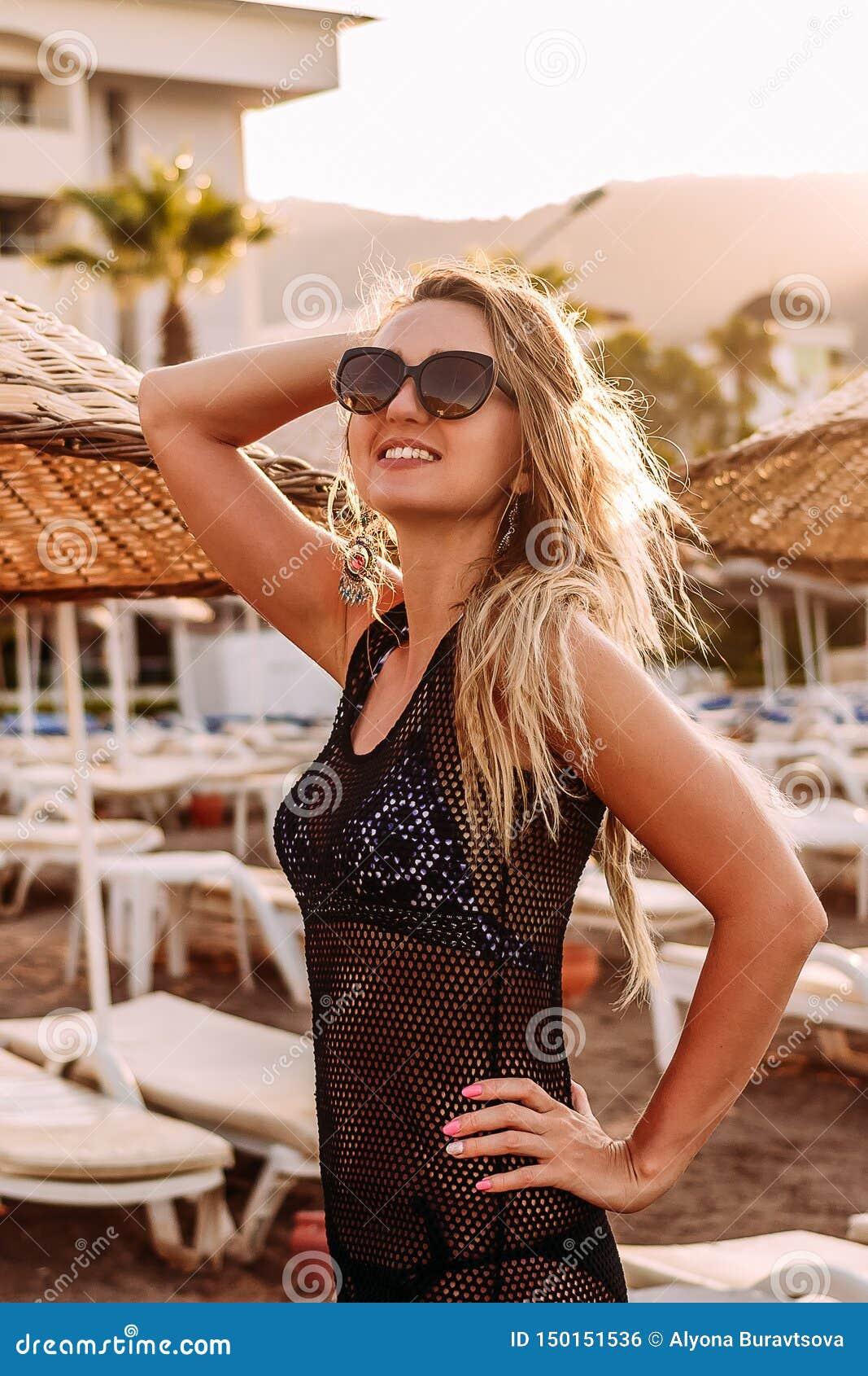 Усмехаясь молодая женщина в солнечных очках представляя на пляже в оконтуренном солнечном свете