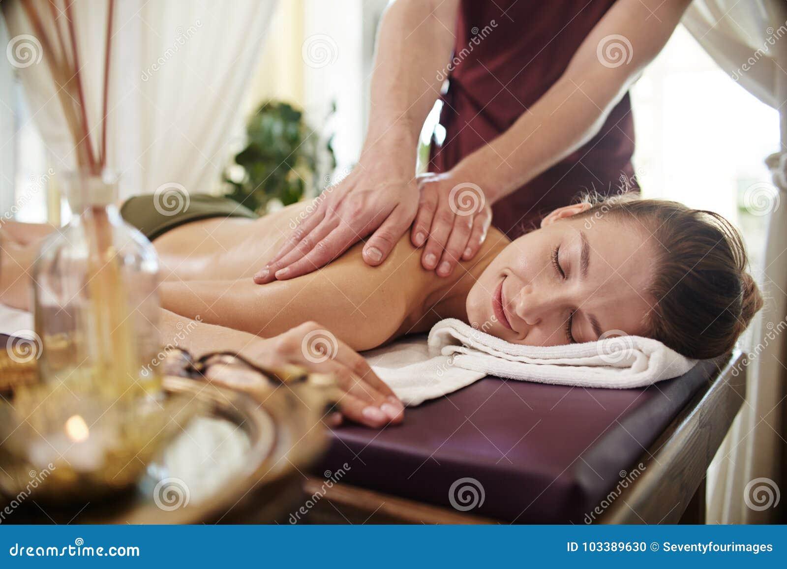 Усмехаясь молодая женщина наслаждаясь массажем в КУРОРТЕ