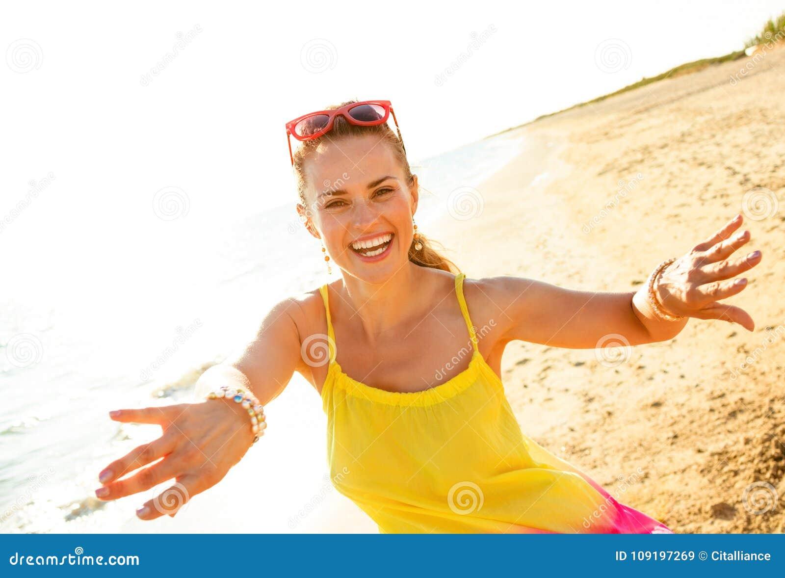 Усмехаясь молодая женщина на пляже в вечере имея время потехи